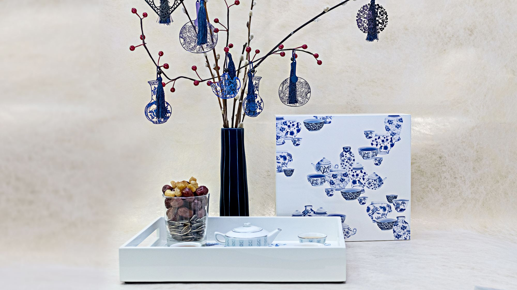 Chinoiserie collection of blue and white ceramics on lacquer box and tray, with oriental charms hanging on pussy willow for the modern home